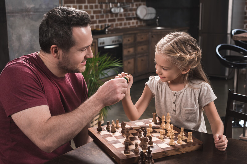 Father daughter play chess